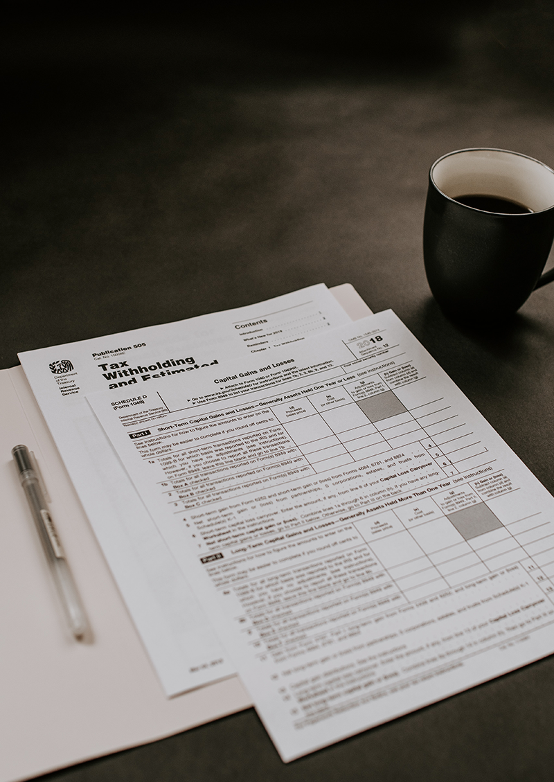 certified divorce financial planner in San Diego, CA,  Image of tax forms on the table with a pen and coffee cup