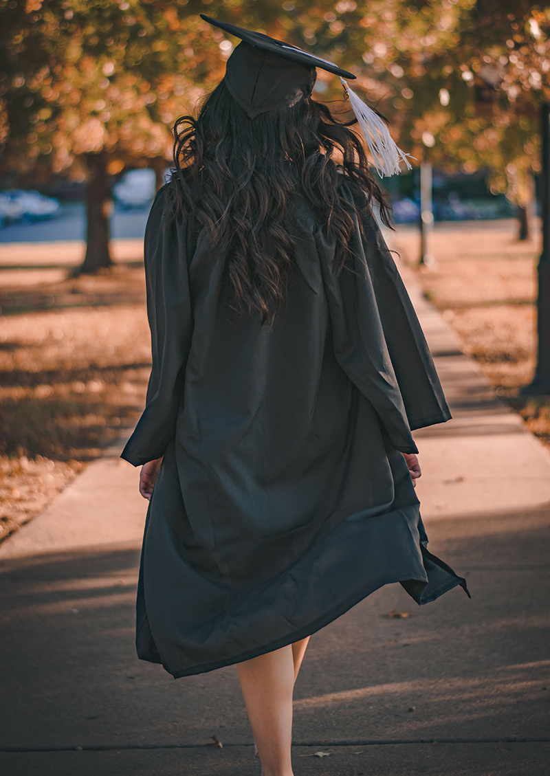 financial planning for college students in San Diego, CA,  Image of a college graduate with a cap and gown walking away