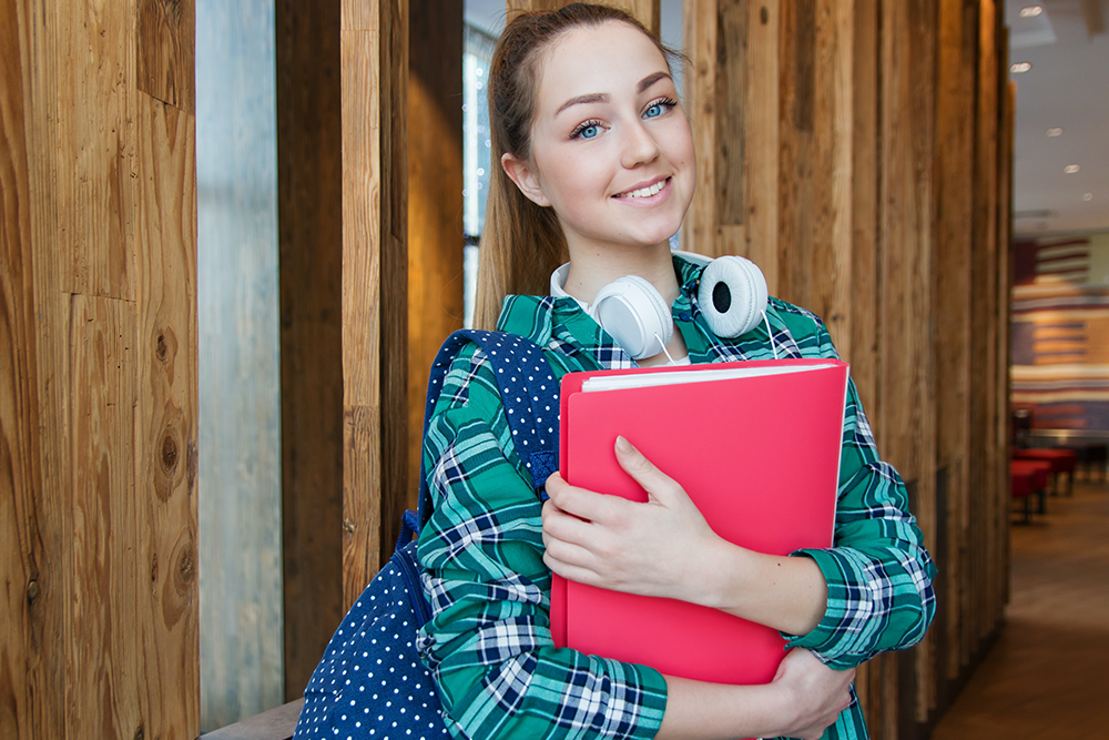 college financial aid strategies in San Diego, CA,  Image of a college student holding her books