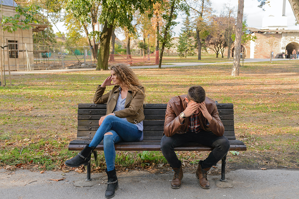 divorce financial advisor in San Diego, CA,  Image of a couple sitting on a bench upset